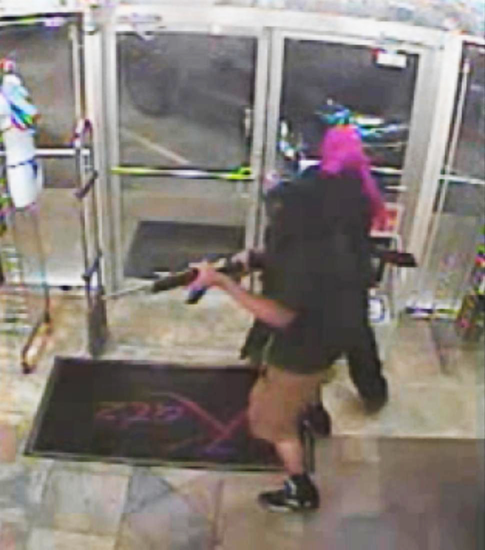 Caught on cam: Clumsy robbers bump into each other, fire shots in lingerie store