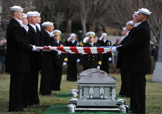 Navy pallbearers remove flags from the caskets of two sailors from the USS Monitor for interment at Arlington National Cemetery.(H. Darr Beiser, USA TODAY)