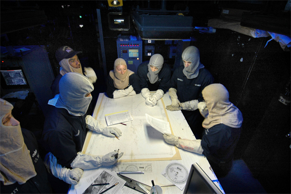 """General Quarters (G.Q.):"" U.S. Navy 051129-N-7883G-005 Combat Direction Center (CDC) watch standers plot a chart during a general quarters (GQ) drill held aboard the conventionally powered aircraft carrier USS Kitty Hawk"